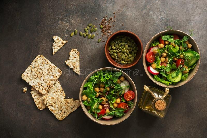 La ensalada vegetariana sana del vegano de los cuencos, garbanzo, lechuga, tomate, las semillas microgreen, del rábano, del pepin fotografía de archivo libre de regalías