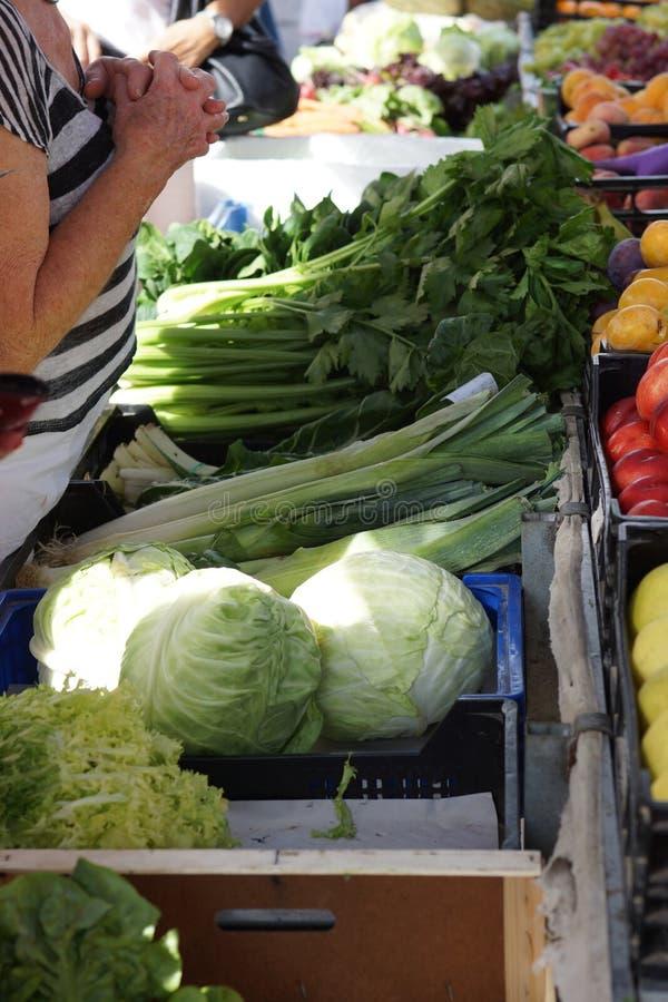 La ensalada y los verdes en el contador en el mercado en España, el cliente espera, las manos abrochadas, como en rezo fotos de archivo libres de regalías