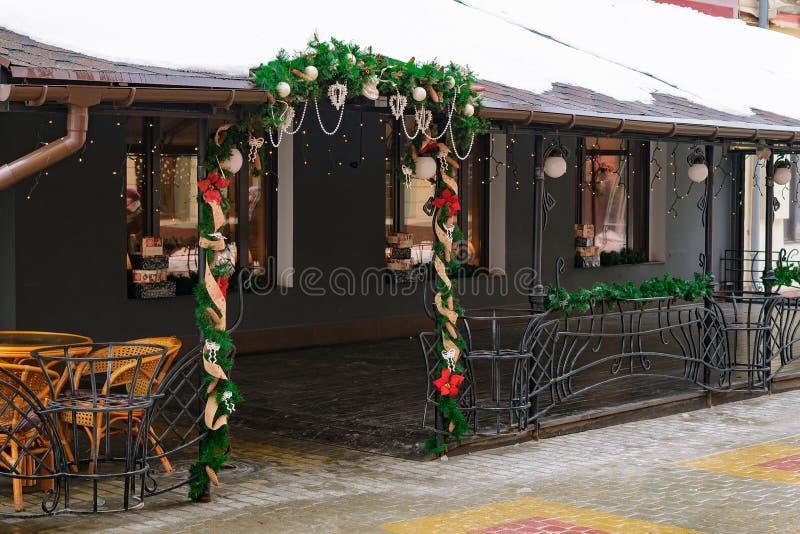 La entrada al café se adorna con las ramas de abetos y de decoraciones del árbol de navidad en el invierno en la calle imágenes de archivo libres de regalías