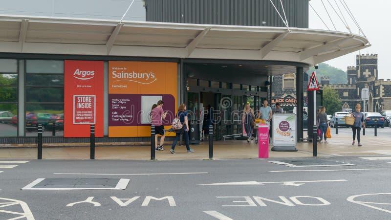 La entrada al ` s de Argos y de Sainsbury se escuda la corte fotografía de archivo