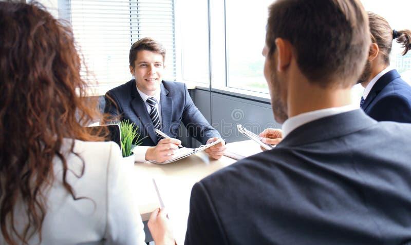 La entrevista de trabajo con el patrón, hombre de negocios escucha las respuestas del candidato imagenes de archivo
