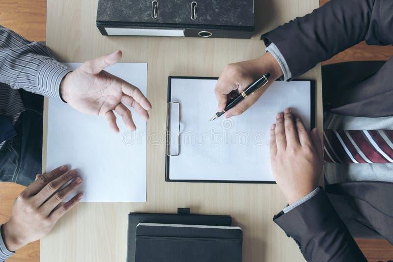 La entrevista de trabajo, los ejecutivos atractivos jovenes sirve hacer preguntas imagen de archivo