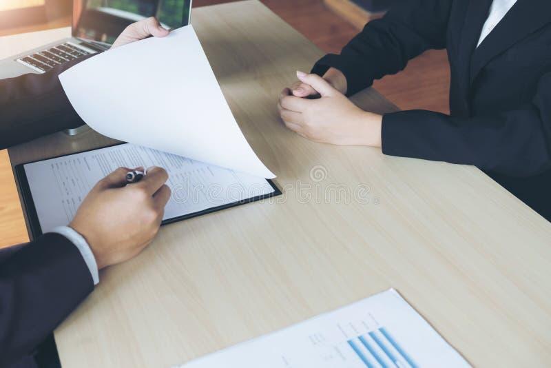 La entrevista de trabajo, los ejecutivos atractivos jovenes sirve la lectura de su resum imagen de archivo