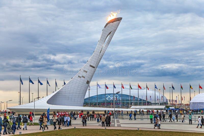 La erección olímpica enorme de la antorcha con la llama ardiente en el parque olímpico era el lugar principal de las olimpiadas d fotos de archivo