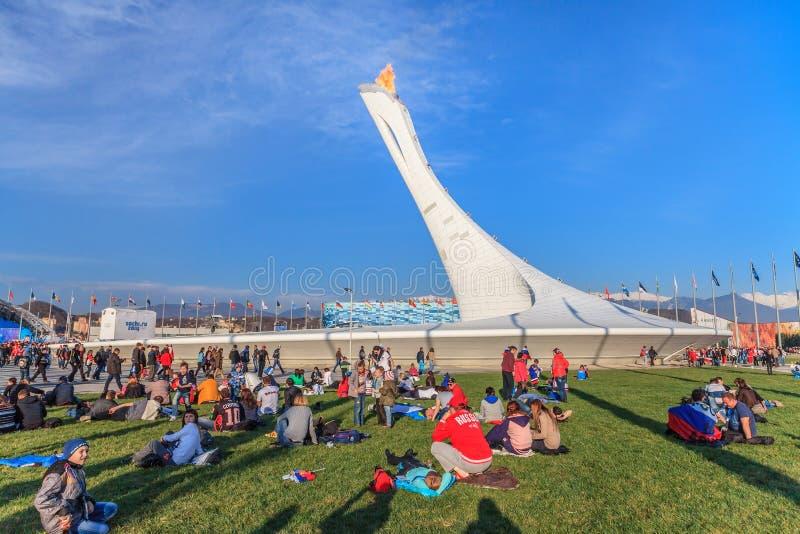 La erección olímpica grande de la antorcha con la llama ardiente en el parque olímpico era el lugar principal de las olimpiadas d fotografía de archivo