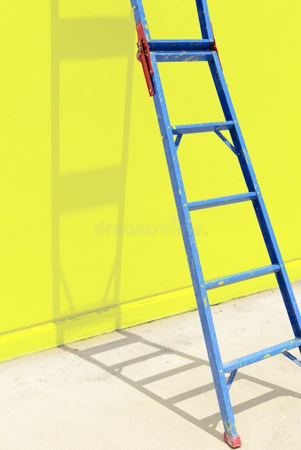 La escalera de acero azul con la pared amarilla fotografía de archivo