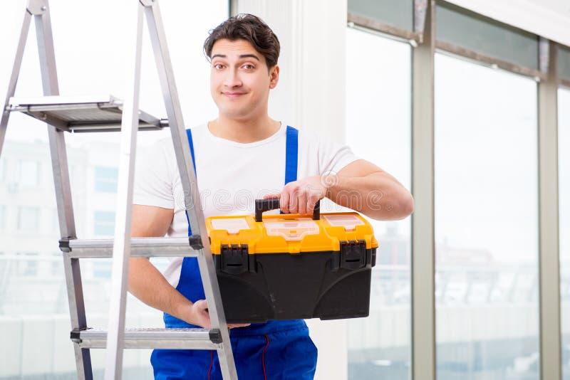 La escalera que sube del reparador joven en el emplazamiento de la obra imagen de archivo