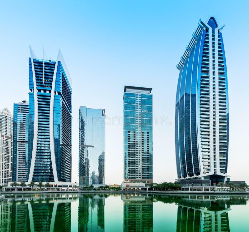 La escena céntrica de la noche de Dubai, lago Jumeirah se eleva imagen de archivo