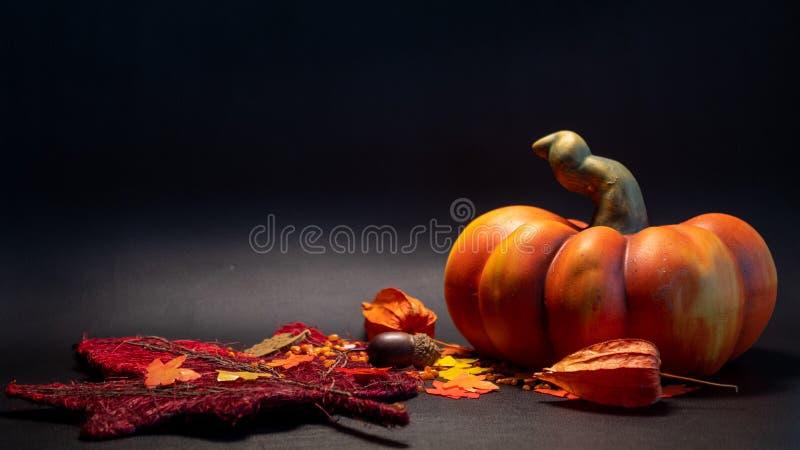 la escena de la decoración de la caída del otoño con la calabaza artificial se va en color anaranjado en fondo negro imágenes de archivo libres de regalías