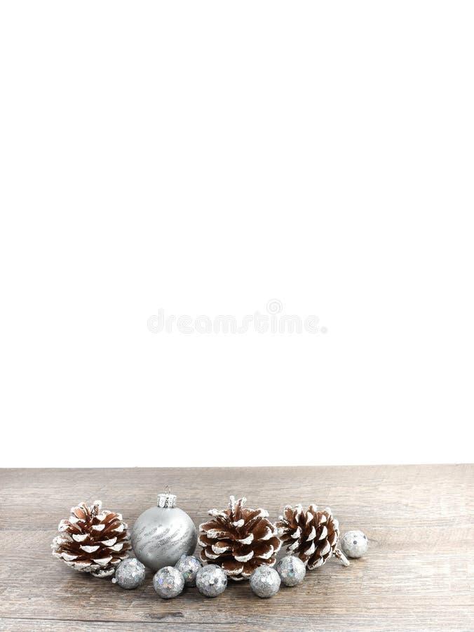 La escena de la Navidad incluyendo conos del pino y los ornamentos en rústico cortejan imagen de archivo libre de regalías