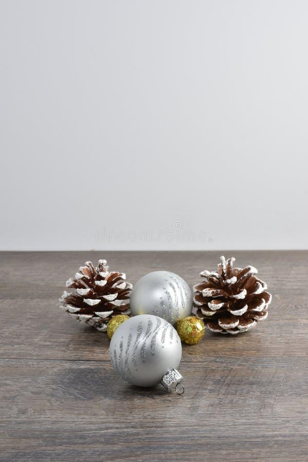 La escena de la Navidad incluyendo conos del pino y los ornamentos en rústico cortejan foto de archivo