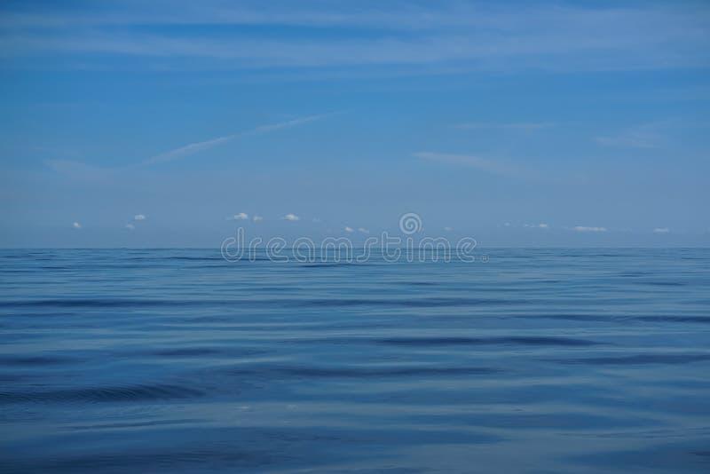 La escena del fondo natural del horizonte brillante del cielo azul y la nube blanca sobre la agua de mar azul profunda ondulan el fotos de archivo libres de regalías