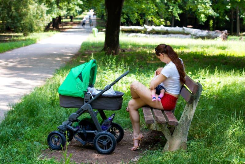 La escena exterior de amamantamiento infantil, la mujer joven atractiva y la nueva madre en mini pantalones cortos rojos está lle fotografía de archivo