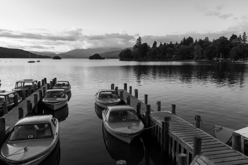 La escena monocromática de la oscuridad de barcos amarró en embarcaderos en Cumbria imagenes de archivo