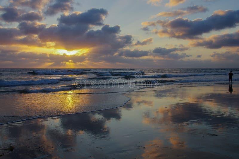 La escena panorámica de la puesta del sol del océano con las nubes reflejó en la playa mojada y la persona que vadeaban imágenes de archivo libres de regalías
