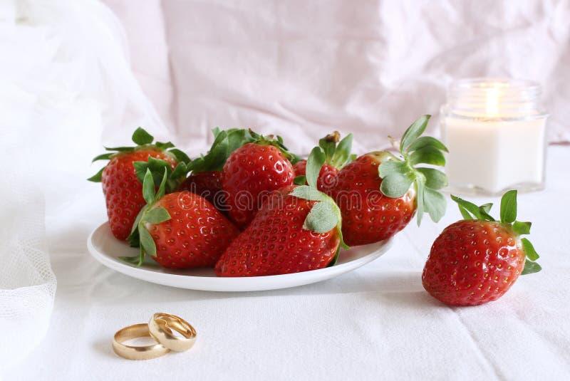 La escena que se casa brillante, la placa de la porcelana con con las fresas frescas y anillo de bodas un fondo blanco Acci?n dis fotografía de archivo libre de regalías