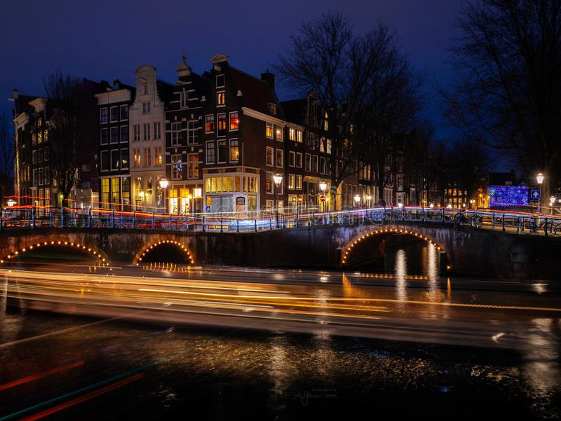 La escena típica del canal de Amsterdam con las casas tradicionales y los rastros ligeros forman los barcos en la noche foto de archivo libre de regalías