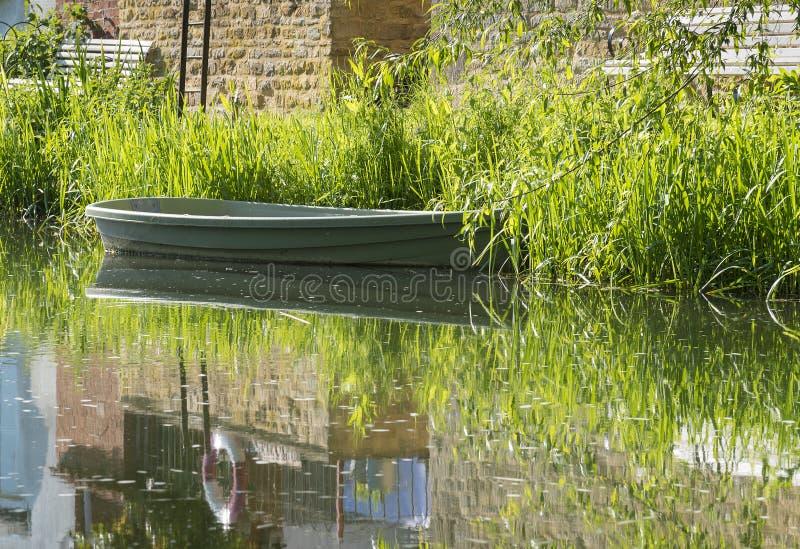 La escena tranquila del río con el barco de rowing vacío amarró en el banco fotografía de archivo libre de regalías