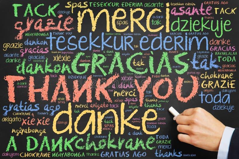 La escritura de la mano le agradece en muchas idiomas fotografía de archivo