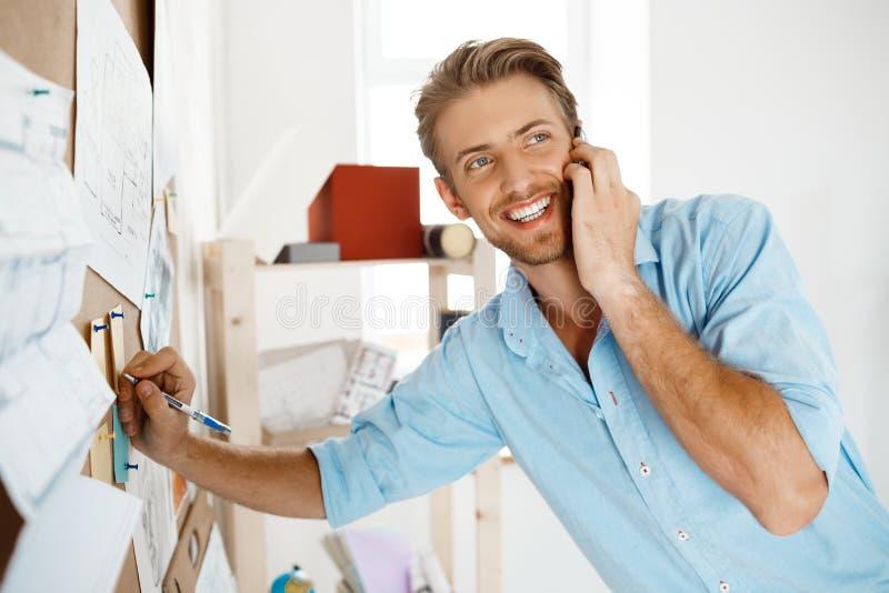 La escritura hermosa joven del hombre de negocios en el papel fijó al corkboard, hablando en la sonrisa del teléfono Fondo de la  imagenes de archivo