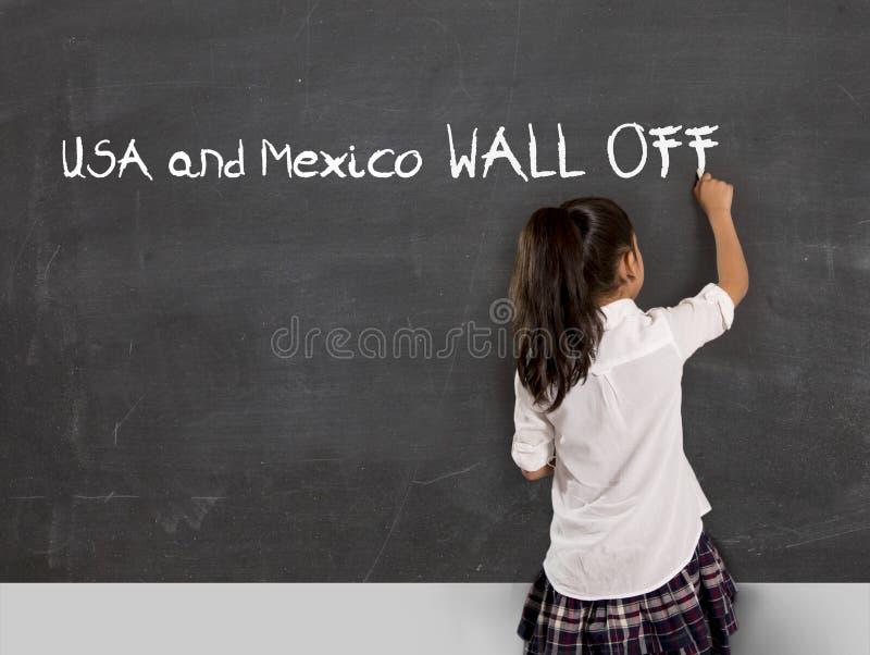 La escritura joven de la colegiala del activista político en la pizarra México y los E.E.U.U. de la sala de clase de la escuela e imagen de archivo libre de regalías