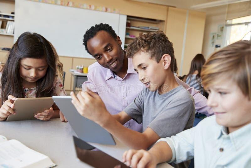 La escuela de ayuda del profesor embroma con las tabletas en clase foto de archivo libre de regalías