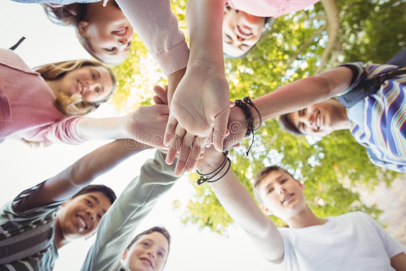 La escuela feliz embroma la formación de la pila de la mano en campus foto de archivo libre de regalías