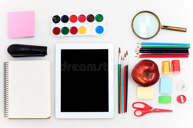 La escuela fijó con los cuadernos, los lápices, el cepillo, las tijeras y la manzana en el fondo blanco fotografía de archivo libre de regalías