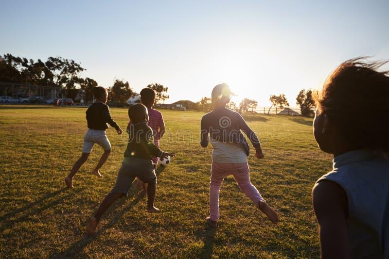 La escuela primaria embroma jugar al fútbol en un campo, visión trasera imagen de archivo