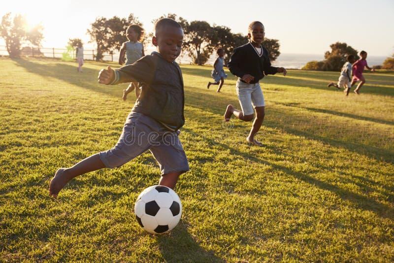 La escuela primaria embroma jugar a fútbol en un campo imágenes de archivo libres de regalías
