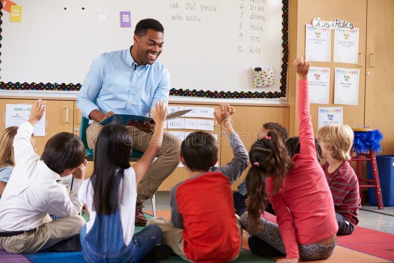 La escuela primaria embroma sentarse alrededor de profesor en una sala de clase imagen de archivo libre de regalías