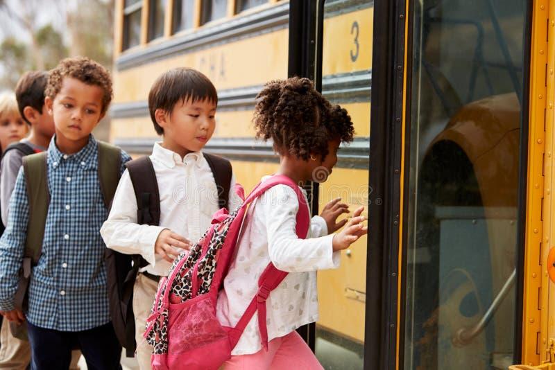 La escuela primaria embroma subir encendido a un autobús escolar imágenes de archivo libres de regalías