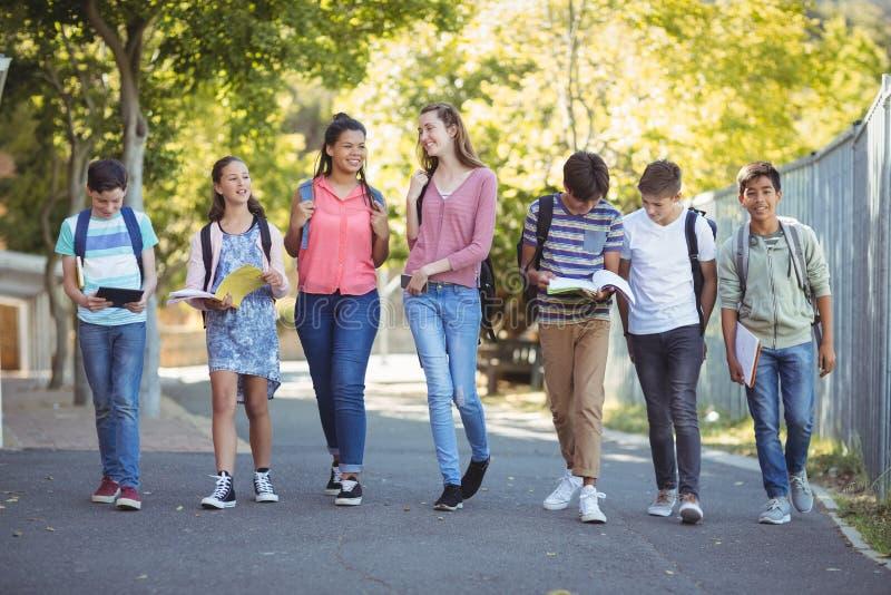 La escuela sonriente embroma caminar en el camino en campus imágenes de archivo libres de regalías
