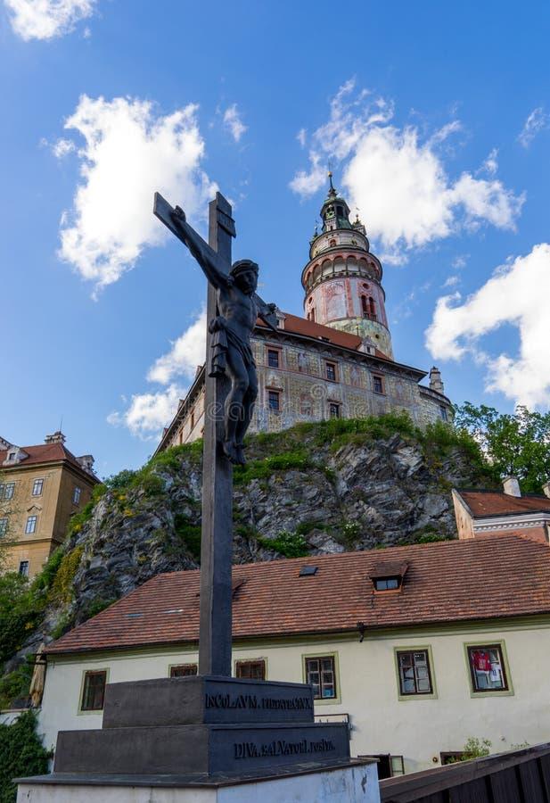 La escultura de Jesús de Cesky Krumlov con el castillo en backgrou imagenes de archivo