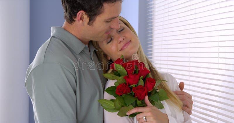 La esposa hermosa consigue sorprendida con el bouqet de rosas imagen de archivo libre de regalías