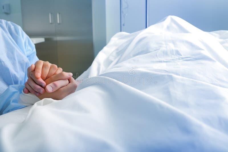 La esposa lleva a cabo la mano del cónyuge difunto en el hospital imagen de archivo
