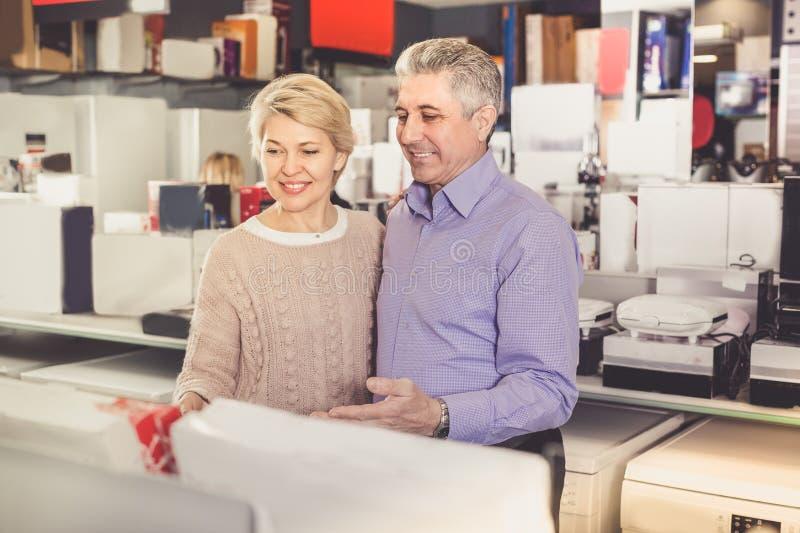 La esposa y el marido están visitando la tienda de los aparatos electrodomésticos para s imagen de archivo libre de regalías