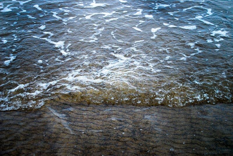 La espuma del mar de la marea baja ondula el fondo fotografía de archivo libre de regalías