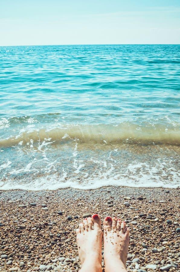 La espuma del mar, las ondas y los pies desnudos de la mujer en una arena varan Piernas de la muchacha que se relajan Los días de imagen de archivo libre de regalías