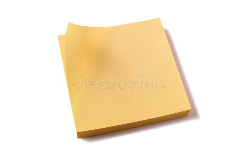 La esquina blanca pegajosa amarilla del fondo del cojín de notas de los posts se encrespó fotos de archivo