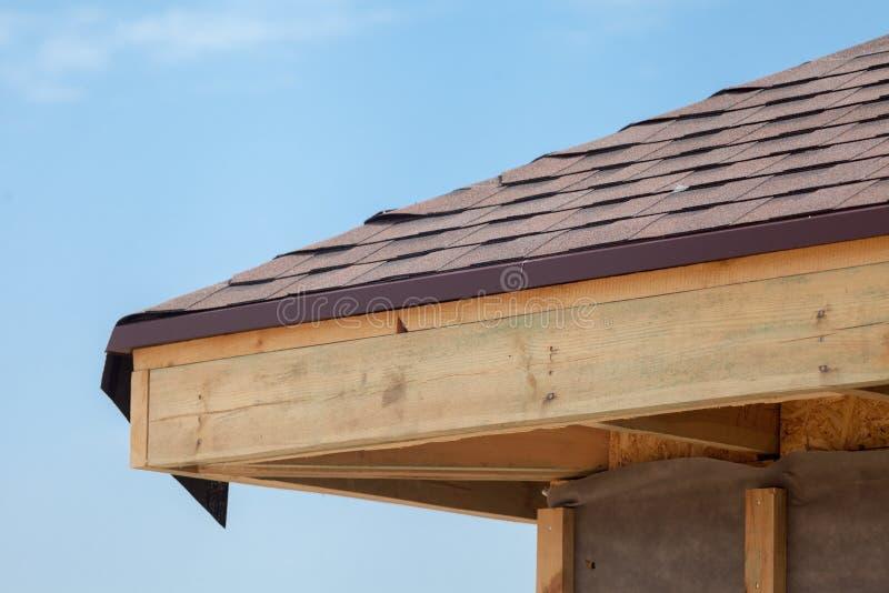 La esquina de la casa con los aleros, los haces de madera y el tejado asfaltan tablas imagen de archivo