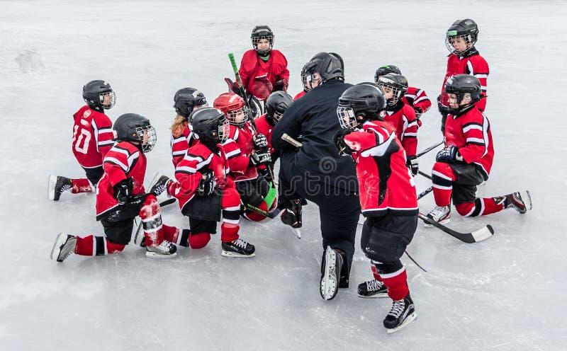 La estación de hockey, niños juega al juego nacional en un carnaval del invierno imagen de archivo libre de regalías