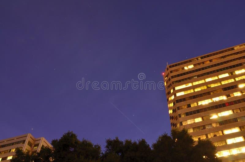 La estación espacial internacional que vuela sobre un cielo nocturno estrellado sobre ciudad foto de archivo