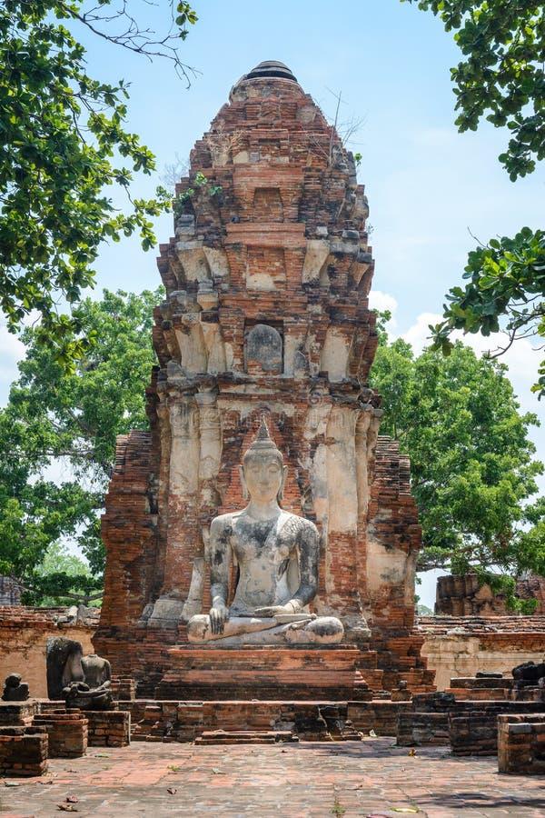 La estatua antigua de Buda del cemento delante de la pagoda arruinada en ancien fotos de archivo libres de regalías