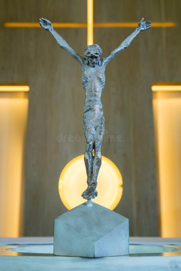 La estatua de bronce de Jesus Christ crucificó en una cruz en una iglesia imagen de archivo