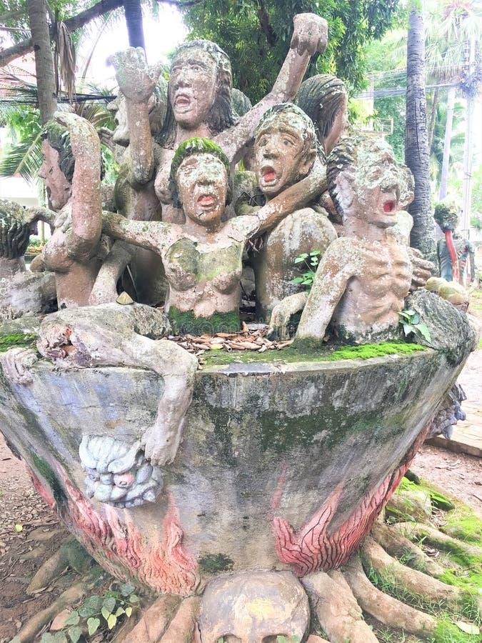 La estatua de la gente en el infierno del abismo se castigue en la cacerola de cobre del fuego foto de archivo