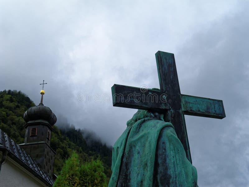 La estatua de Jesus Christ con la cruz continuó hombros foto de archivo