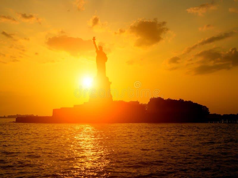 La estatua de la libertad en la puesta del sol foto de archivo