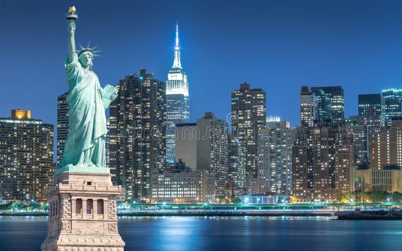 La estatua de la libertad con paisaje urbano en Manhattan en la noche, New York City fotografía de archivo libre de regalías