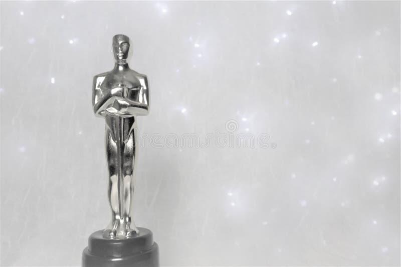 La estatua de oro del éxito y de la victoria en un fondo blanco foto de archivo